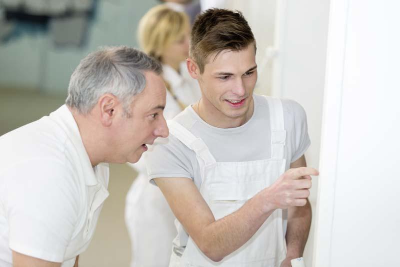Nachwuchs im Bauhandwerk oder Ausbauhandwerk lernt vom erfahrenen Meister erste Handgriffe.