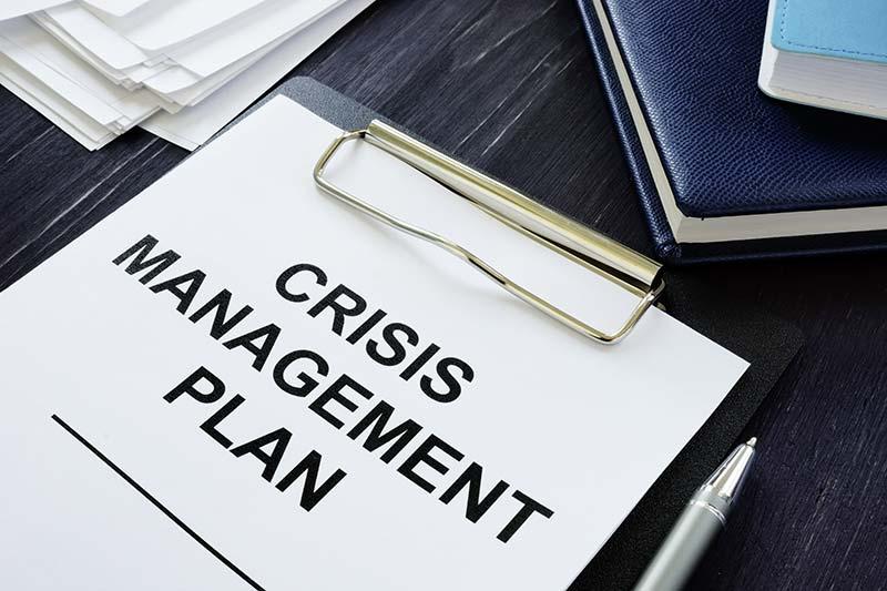 Auf einem Tisch liegt ein Krisenmanagementplan, der Unternehmen in Schwierigkeiten bei der Sanierung und Restrukturierung hilft.
