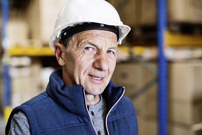 Arbeiter mit Helm schaut in die Kamera und symbolisiert damit die große Anzahl von Arbeitnehmern, die in den nächsten Jahren in den Ruhestand gehen.